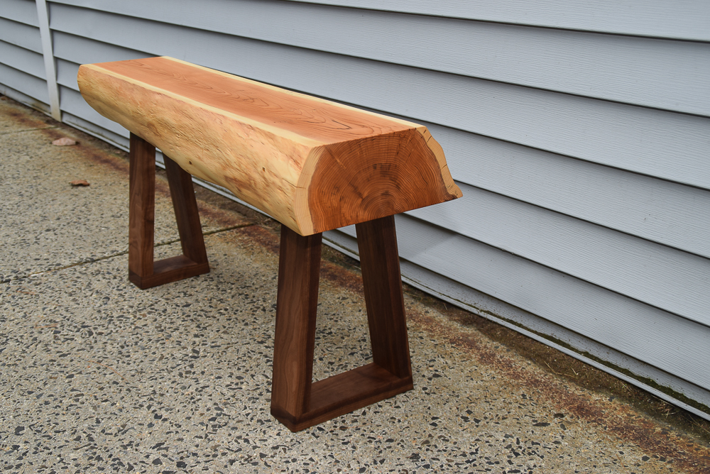 live edge yew bench with walnut legs viewed at an angle