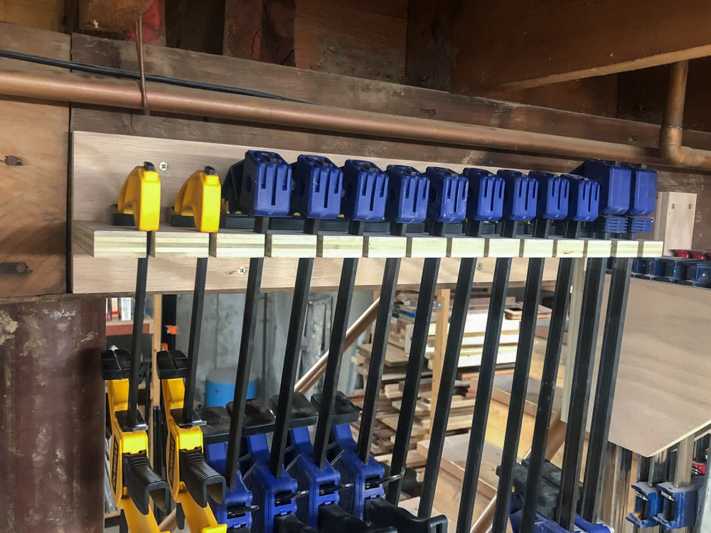 quick clamps hanging in the oak plywood quick clamp rack